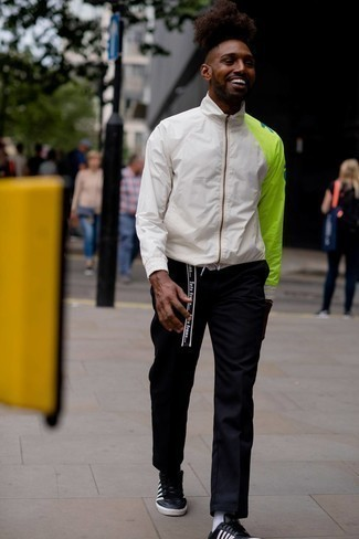 Black and White Leather Low Top Sneakers Outfits For Men: Wear a white print windbreaker with black chinos for a casual and cool and trendy ensemble. Let your styling skills truly shine by finishing this outfit with black and white leather low top sneakers.
