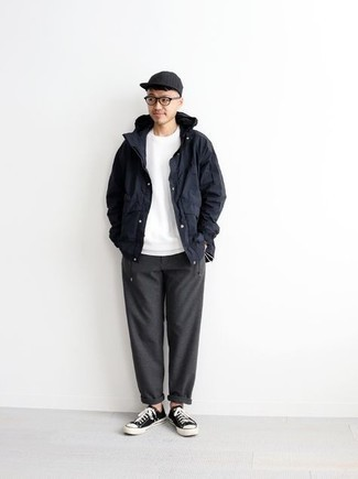 Windbreaker Outfits For Men: This pairing of a windbreaker and charcoal chinos is a safe and very fashionable bet. Look at how well this ensemble is rounded off with a pair of black and white canvas low top sneakers.