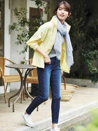 How to wear: yellow windbreaker, navy skinny jeans, white canvas low top sneakers, tan straw tote bag