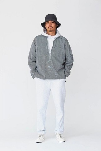 Bucket Hat Outfits For Men: This edgy combination of a grey windbreaker and a bucket hat couldn't possibly come across as anything other than seriously dapper. For a classier twist, slip into a pair of white canvas low top sneakers.