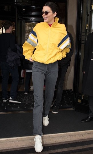 How to Wear Grey Jeans For Women: We all look for functionality when it comes to fashion, and this combo of a yellow windbreaker and grey jeans is a perfect example of that. Complement this look with a pair of white leather low top sneakers et voila, this look is complete.
