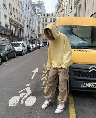 Men's Outfits 2021: This pairing of a yellow hoodie and khaki cargo pants is irrefutable proof that a pared down casual outfit can still be seriously sharp. For extra style points, complement your getup with white and red leather high top sneakers.