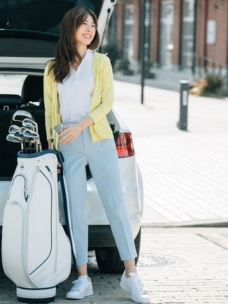 How to Wear White Leather Low Top Sneakers For Women: A yellow hoodie and light blue tapered pants are a cool combo to have in your casual styling rotation. Slip into a pair of white leather low top sneakers and you're all done and looking stunning.