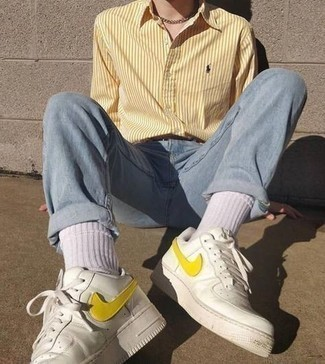 Men's Outfits 2021: Wear a yellow vertical striped long sleeve shirt and light blue jeans to achieve a cool and casual getup. When not sure as to what to wear on the footwear front, stick to a pair of white leather low top sneakers.