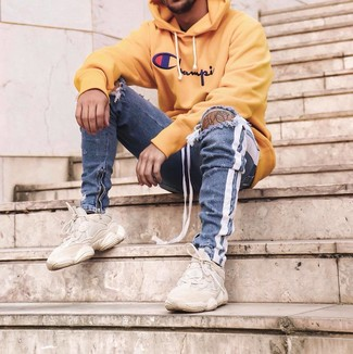 How to wear: yellow print hoodie, blue ripped skinny jeans, beige athletic shoes