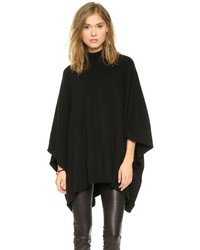 Pairing black denim shorts with a poncho is a comfortable option for running errands in the city.